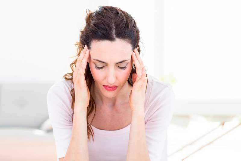 Mujer con dolor de cabeza por mala vibra